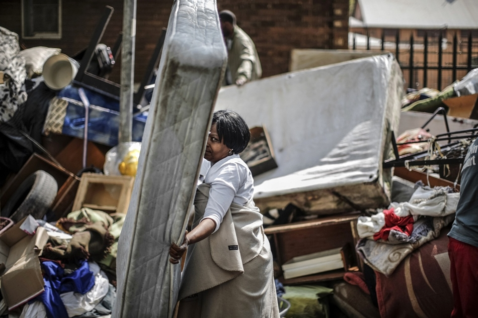afp. hét képei - Johannesburg, Dél-Afrika, 2015.09.01. kilakoltatás, A woman salvages a mattress from a pile of furnitures left in a street of the popular down town district of Hillbrow on September 1, 2015 following the execution of an eviction order on