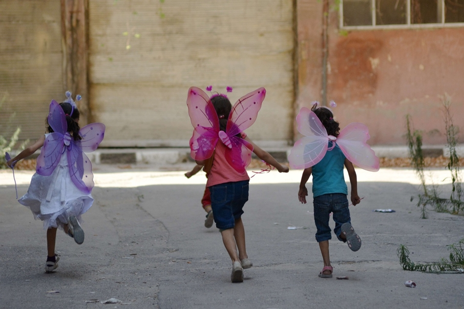 afp. hét képei - Damaszkusz, Szíria, 2015.09.31. Palesztin lányok jelmezben, Palestinian girls wearing costumes play in the besieged Yarmuk refugee camp in the Syrian capital Damascus on August 31, 2015. Several thousand civilians have been able to leave